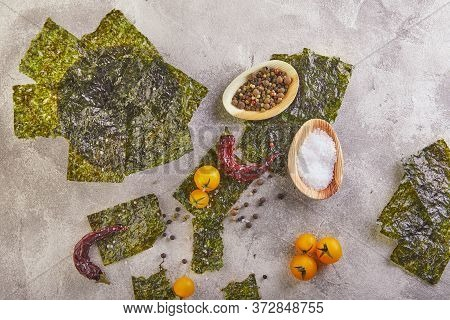Crispy Nori Seaweed With Cherry Tomatoes And On Gray Concrete. Japanese Food Nori. Dried Sheets Of S