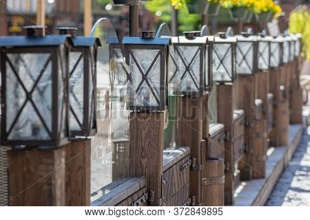 Vintage Wooden Fence With Old Style Lanterns. Outdoor Lighting Decoration.