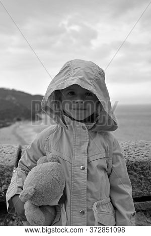 Little Girl With Teddy Bear Is Wearing A Raincoat Jacket With Hood Against A Stormy Sky. Childhood C