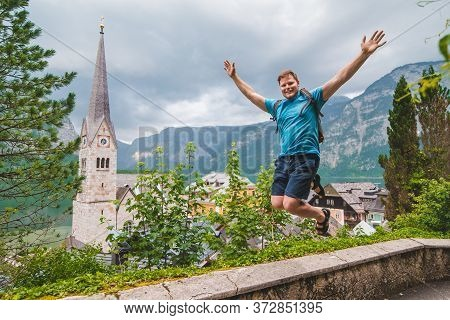 Happy Man Tourist Standing With Rising Up Hands Looking At Hallstatt City From Above