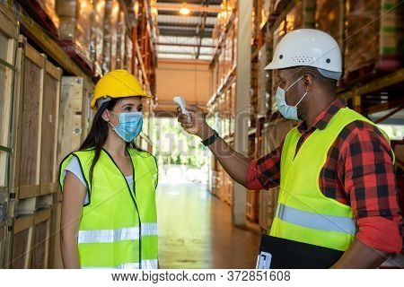 Warehouse Worker,body Temperature Check, Prevent Virus Concepts In Preventing Contagious Diseases. C