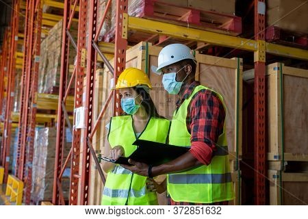 Group Warehouse Workers Wearing Protective Mask To Protect Against Covid-19 Working In Industrial Fa