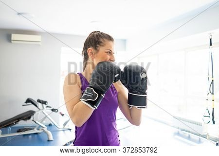 Pretty attractive woman kickboxing in gym