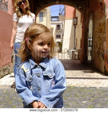 Portrait Of Pretty Little Girl In The Italian Village. Her Mum On The Background. San Felice Circeo,