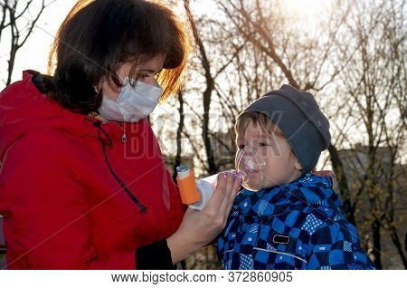 A Small Boy With Illness Bronchial Asthma Getting Treatment With Aerosol Inhaler From His Mama Outdo