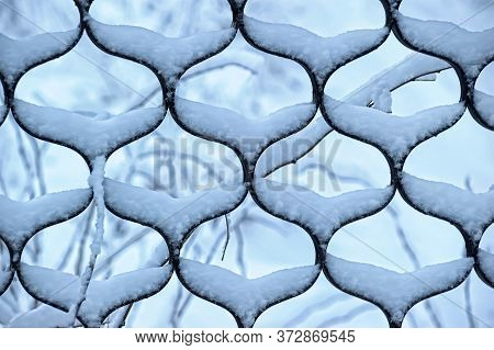 Snow On The Grating Fence Close Up