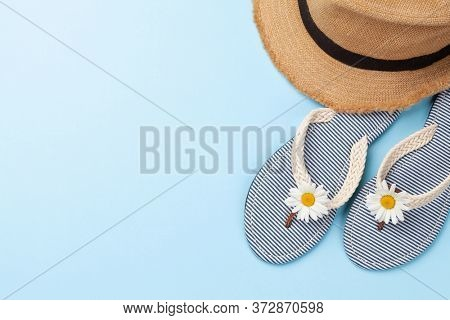 Summer vacation items and accessories. Flip flops and sun hat on blue background. Top view flat lay with copy space