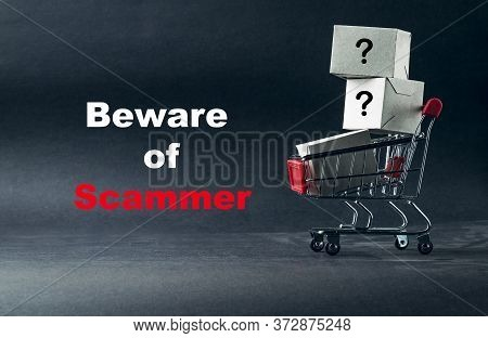 Words Beware Of Scammer On Dark Background With Shopping Cart. Business, Copy Space And Online Shopp