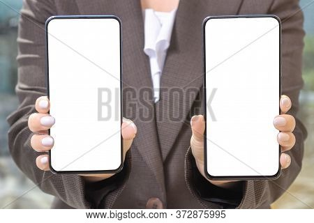 Mockup Cellphone. Woman In A Suit Holding Two Cellphones. The Face Is Not Visible
