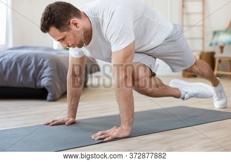 Workout Concept. Sporty Man Training At Home Doing Running Plank Exercise In Bedroom. Selective Focu