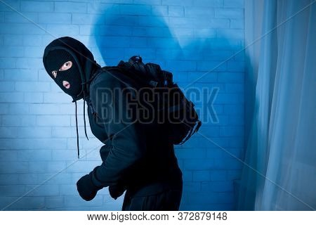 Burglary Concept. Sneaky And Scared Intruder Wearing Black Balaclava Hat Lurking In The Dark, Lookin
