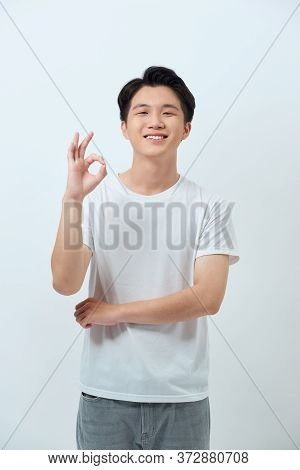 Everything Is Ok! Happy Young Man Gesturing Ok Sign And Smiling