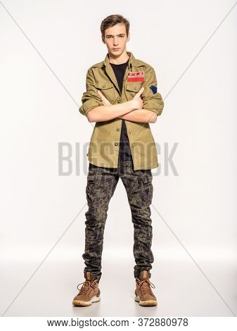 Young man in camouflage clothing. Rookie in army clothes. Teenager in khaki military clothing poses in a studio on a white background. Conscript in camouflage, isolated.