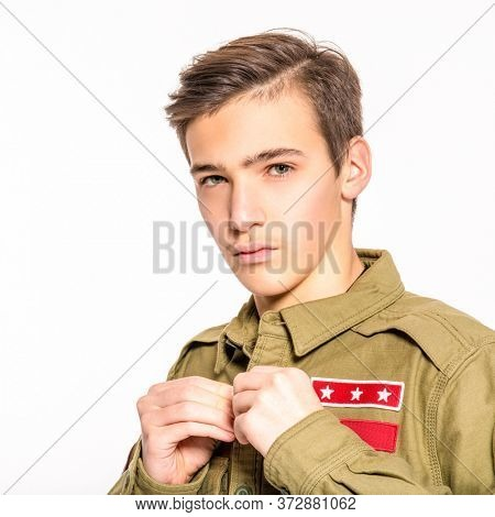 Portrait of an young man in camouflage clothing. Rookie in army clothes. Teenager in khaki military clothing poses in a studio on a white background. Conscript in camouflage, isolated.