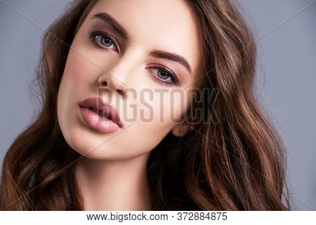 Portrait of a beautiful woman with a long hair. Beautiful face of sexy young woman. Young  brunette model with  beautiful hair, isolated on white background. Young girl with clean fresh skin of a face