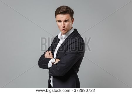 Side View Of Puzzled Young Business Man In Classic Black Suit Shirt Isolated On Grey Background. Ach