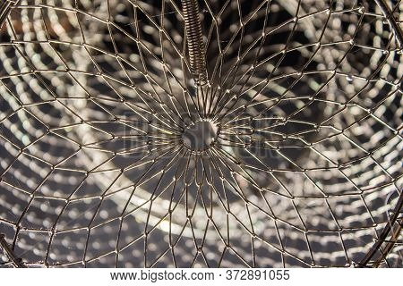 Close Up Macro Of Shiny Metal Net For Fish Trap. Detailed Fragment Of A Fishing Basket Net
