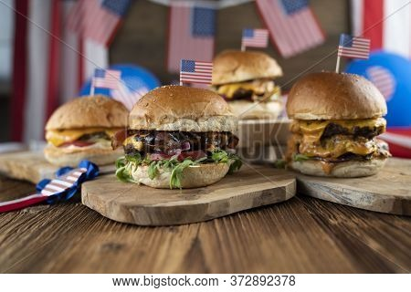 Fourth Of July Celebration. American Flag And Decorations. Burgers On Rustic Wooden Table.