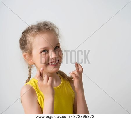 Lovely Little Girl With Cute Pigtails Looking Up Showing A Cheerful Smile And Holding Up Hands With