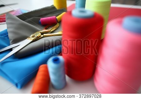 Close Up Of Seamstress Workplace With Colorful Sewing Threads, Gray And Blue Fabrics And Sewing Scis