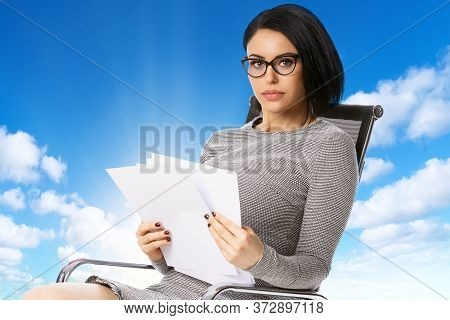 Pensive Young Business Woman In Glasses Sitting On Chair With Paper Documents Over Blue Sky Backgrou