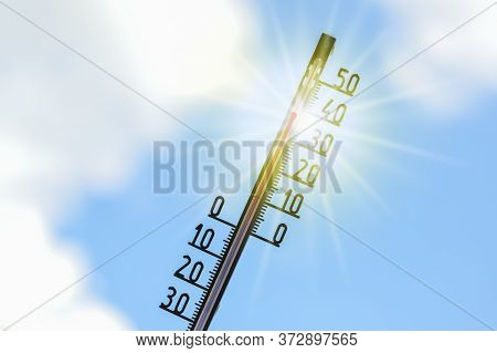 Thermometer Shows Heat In The Summer Season Against A Blue Sky With Clouds And Sun Rays, Weather Phe