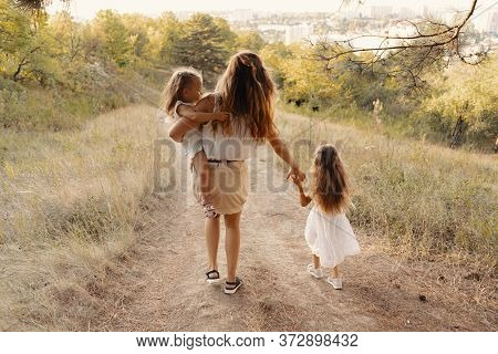 A Beautiful Young Woman Playing With Her Daughter. Happy Family Spends Their Day In The Nature. Thre