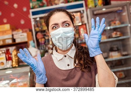 Small Businesses During The Pandemic. A Female Worker In A Medical Mask And Rubber Gloves, Eyes Bulg