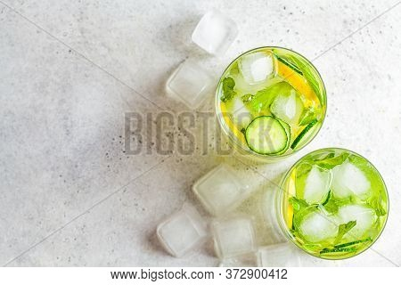 Detox Sassy Water With Cucumber And Lemon In Glasses, Light Background. Healthy Eating Concept.