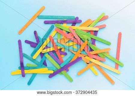 Colorful Wood Sticks Used For Creating Art Shapes/objects. Rainbow Color Sticks On A Blue Background