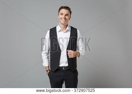 Smiling Cheerful Young Business Man In Classic Black Waistcoat Shirt Posing Isolated On Grey Wall Ba