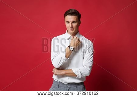 Handsome Young Business Man In White Shirt, Gray Pants Posing Isolated On Bright Red Wall Background