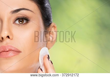 Beautiful Brunette Woman With Cotton Pad Over Green Blurred Background With Copy Space. Health And B
