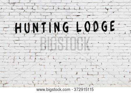 White Brick Wall With Inscription Hunting Lodge Handwritten With Black Paint