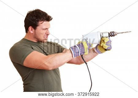 Construction worker with drill drills with a strained face
