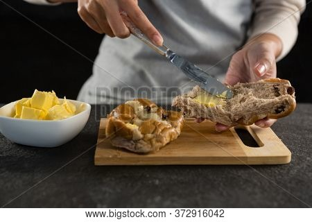 Close-up of woman applying butter over multigrain bun slice
