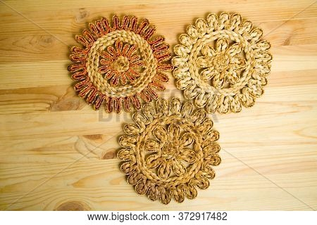 Three different coasters made of bast on a worktop from above