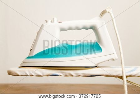 Bright iron stands on an ironing board