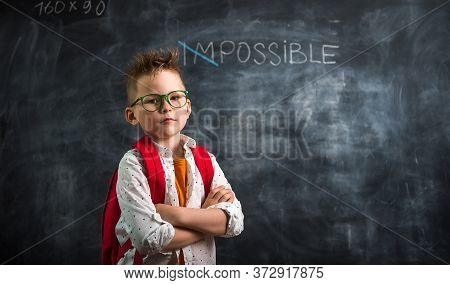 Very Confidant Little Boy With Possible Impossible Words On A Blackboard