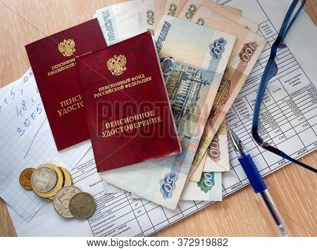 On The Table Are Two Pension Certificates, Paper And Metal Rubles, A Receipt For Utility Bills, Note