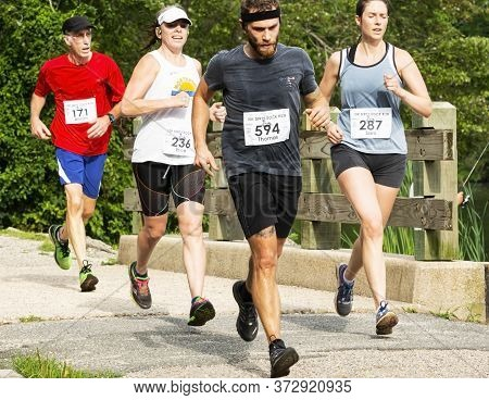 Babylon, New York, Usa - 12 August 2018: A Group Of Runners Running The Dirty Sock 10k On A Hot Summ