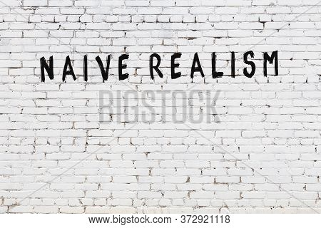 Word Naive Realism Written With Black Paint On White Brick Wall.