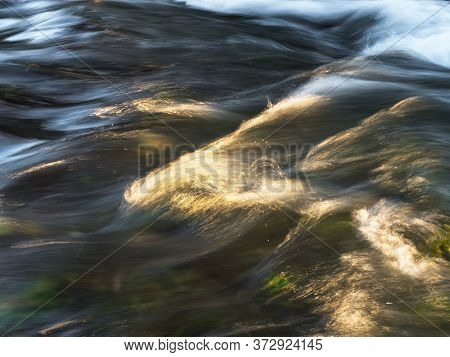 The Stream Of Water In Blur. A Stream Of Water Backlit By The Rays Of The Sun, Breakers On The Surfa