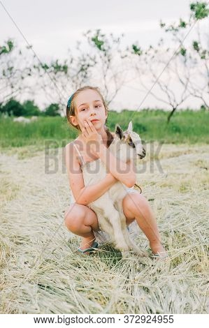 Girl With Baby Goat On Farm Outdoors. Love And Care. Village Animals. Happy Child Hugs Goat, Concept