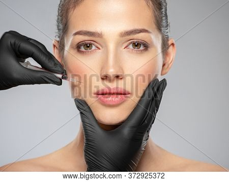 Young caucasian woman getting  cosmetic injection near the eyes. Beautiful woman gets  injection in her face. Adult girl gets cosmetic injection of  in a clinic. Beauty treatments