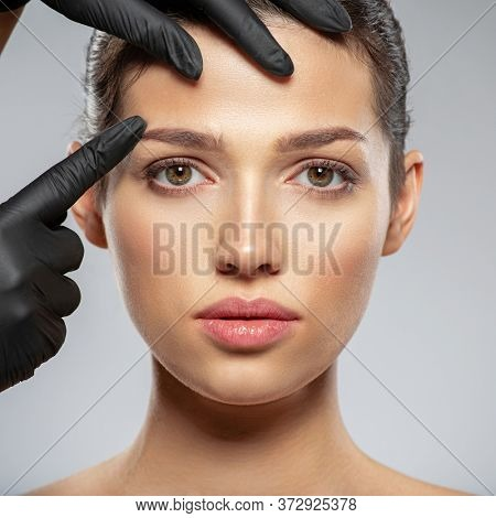 Face skin check before plastic surgery. Beautician touching woman face. Doctor checks a skin before plastic surgery. Beauty treatments. Plastic surgery doctor is touching face of a patient by hands