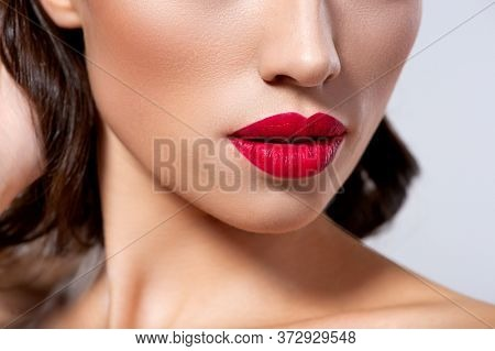 Photo of closeup of a part of a woman's face. Lips of a beautiful girl with bright red lipstick. Macro image of the girl's lips painted with red lipstick.