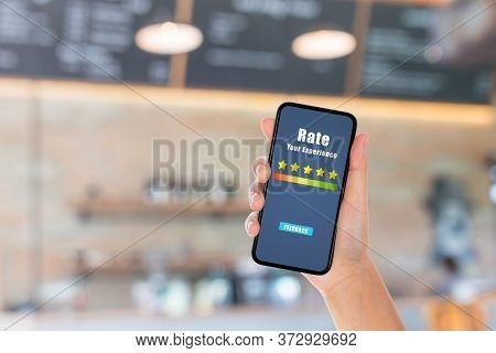 Customer Feedback And Satisfaction Concept : Hand Holding Smartphone To Give Best Service Ranking Wi