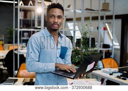 Confident African Team Leader, Standing With Laptop In Modern Creative Office, Looking At Camera Wit