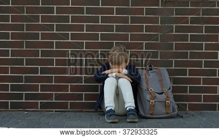 School Bully. Kid Boy Sitting Near Wall And Cry Because Of Bullying. Back To School. Pupil